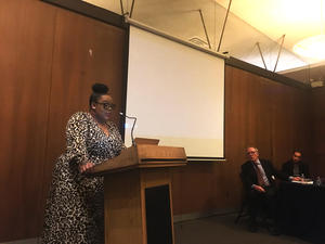 Stephanie-Jones Rogers, speaks at a podium in foreground. Thomas Laqueur and David Henkin are visible in background.