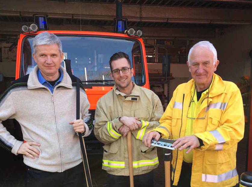 Photo of three smiling people, two of whom are in firefighting uniforms.