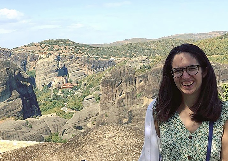 Image of a person smiling in the forefront, standing before a sunny, landscape in the background.