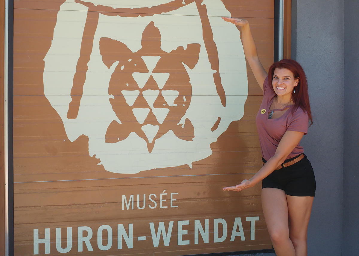 "Image of a person in front of a mural that reads ""Musée Huron-Wendat"""