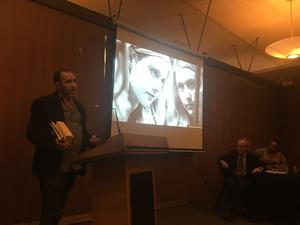 David Henkin stands in front of projected video clip of Little Women.